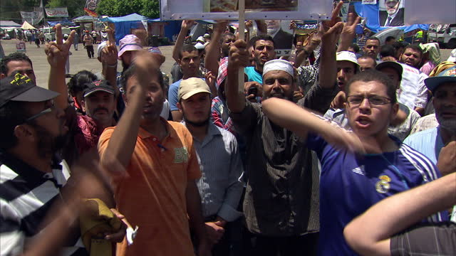 vídeos de stock, filmes e b-roll de exterior shots muslim brotherhood supporters chanting singing at rabaa protest camp with banners posters morsi supporters chanting on july 28 2013 in... - arab spring