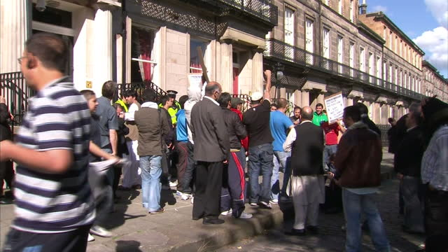 exterior shots muslim protestors gather outside the us consulate building in edinburgh & demonstrate over the planned burning of the koran by the... - pastor stock videos & royalty-free footage