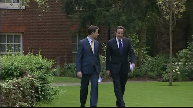 Exterior shots Nick Clegg and David Cameron walk through Downing Street Rose garden and approach gathered press on May 12 2010 in London England