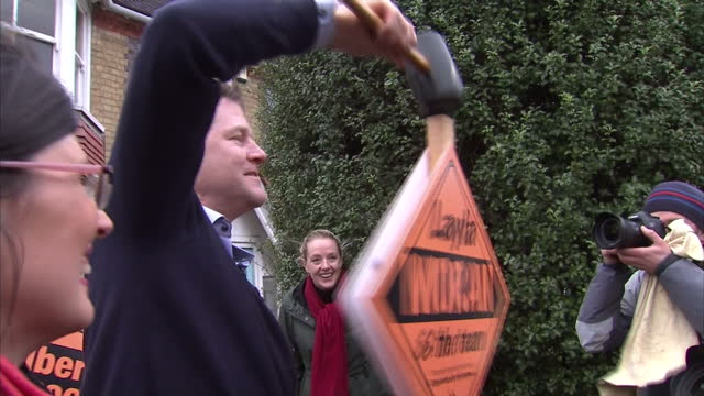exterior shots nick clegg liberal democrat leader struggling to hammer 300th lib dem election stake board into ground he jokes 'i've been told to... - ニック クレッグ点の映像素材/bロール