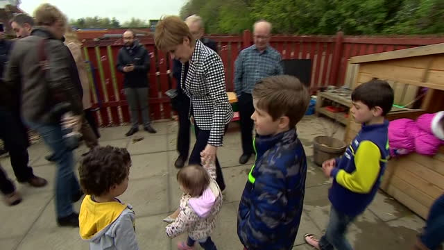 exterior shots nicola sturgeon first minister of scotland visits daycare to campaign for the snp in the general election vote walks into outdoor area... - barnomsorg bildbanksvideor och videomaterial från bakom kulisserna