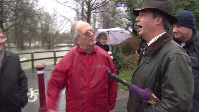 exterior shots nigel farage leader of ukip on visit to flood affected areas of chertsey talks with local residents on in chertsey united kingdom - 英国独立党点の映像素材/bロール