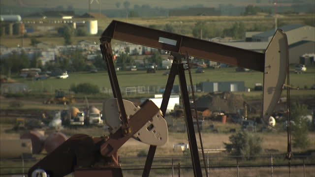 exterior shots nodding donkey pumpjack in oil field with various buildings in background on august 3 2009 in north dakota united states - 合意点の映像素材/bロール