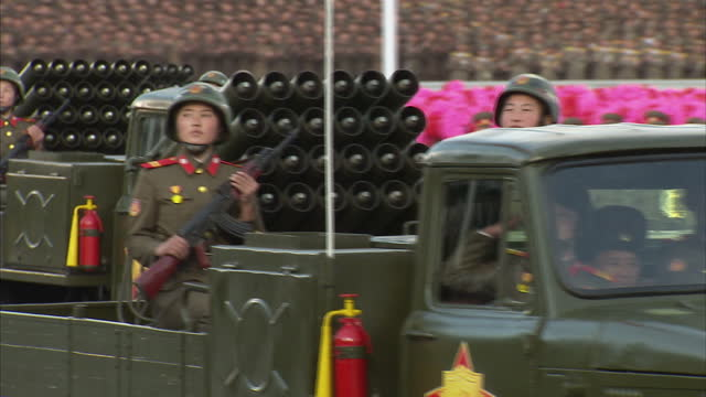 exterior shots north korean military vehicles with mounted missile launchers and soldiers sitting on side of vehicles at workers party 70th... - military parade stock videos & royalty-free footage