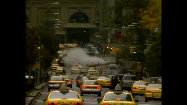 Exterior shots NYC yellow taxi cabs driving along street in traffic with steam rising from steam grates on November 05 1996 in New York City