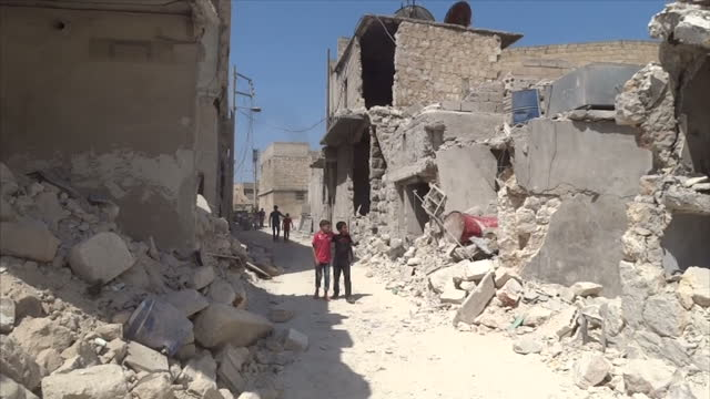 Exterior shots of 2 young boys walking with arms around each other looking at the damage to buildings from a barrel bomb attack that hit the area on...