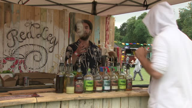 Exterior shots of a barman mixing cocktails and juggling with bottles of spirits at a food festival on 23 June 2017 in Birmingham United Kingdom
