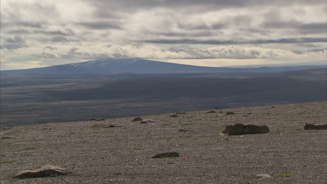 exterior shots of a barren rocky, volcanic landscape with distant snow capped mountains and clouds rolling overhead on august 24, 2014 in reykjavik,... - distant点の映像素材/bロール