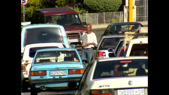 exterior shots of a beggar with a placard walking past cars at a traffic junction in soweto on january 30, 2004 in soweto, south africa. - retrovirus video stock e b–roll