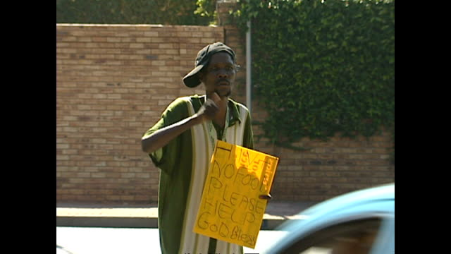 exterior shots of a black beggar in soweto with a placard reading 'hiv+ no food, please help' as cars pass on january 30, 2004 in soweto, south... - retrovirus video stock e b–roll