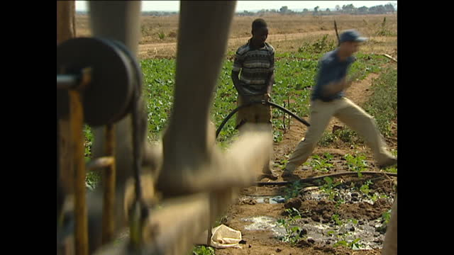 vídeos de stock, filmes e b-roll de exterior shots of a boy using his legs and feet to pump water from a nearby well to water the crops on august 12 2002 in zambia - poço