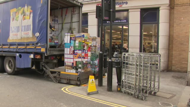 exterior shots of a branch of tesco metro supermarket as workers unload a delivery from a lorry on 21 march 2020 in london, united kingdom - unloading stock videos & royalty-free footage