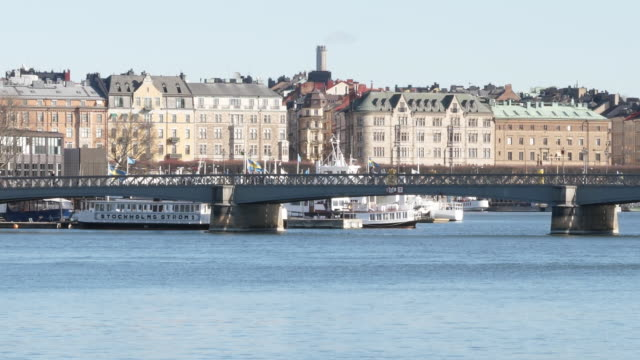 exterior shots of a bridge with people walking across stockholms ström with various traditional buildings lining its banks on 3 april 2020 in... - stockholm stock videos & royalty-free footage