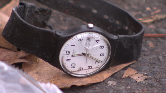 exterior shots of a broken wristwatch on the ground outside the bataclan theatre, discarded blood covered gloves of paramedics, a discarded catheter... - strumento medico video stock e b–roll