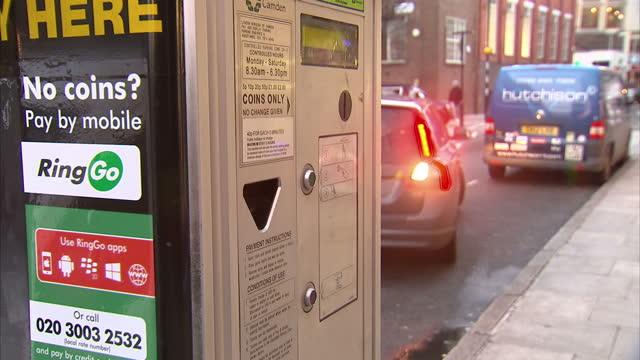 vídeos de stock e filmes b-roll de exterior shots of a car parking near a 'pay and display' ticket machine on a london street, and a man using a mobile phone next to a ticket machine,... - estacionar