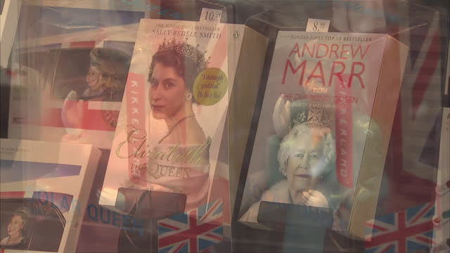 exterior shots of a cardboard depiction of queen elizabeth ii in the window of a book shop in berlin, along with biographies of the queen and waving... - 2015 stock-videos und b-roll-filmmaterial