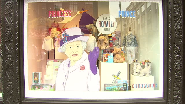 Exterior shots of a Carry me Home shop display showing a picture of the Queen with the caption one is Royally excited and baby clothes displayed at...