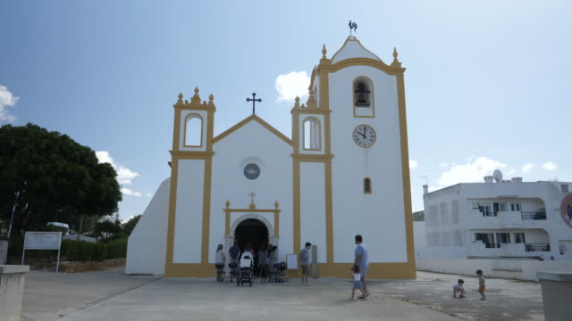 exterior shots of a catholic church in praia da luz as people walk in and out on 11 september 2020 in praia da luz, portugal - マデリン・マクカーン失踪事件点の映像素材/bロール