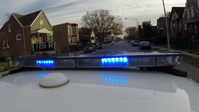 Exterior shots of a Chicago police car responding to an emergency driving quickly through the streets of Chicago with sirens sounding and blue lights...