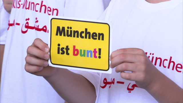 exterior shots of a children's choir singing songs and wearing 'homs munchen' in support of syrian refugees on july 22 2016 in munich germany - シリア難民問題点の映像素材/bロール