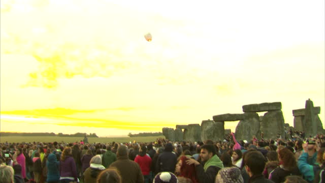vídeos y material grabado en eventos de stock de exterior shots of a 'chinese lantern' floating away in the sky over stonehenge as crowds watch the sun rise during summer solstice celebrations.>> on... - solsticio de verano