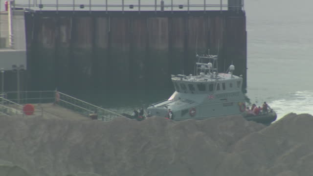 exterior shots of a coast guard patrol boat sailing into dover port with rescued migrants on deck on 11 august 2020 in dover united kingdom - 船の一部点の映像素材/bロール