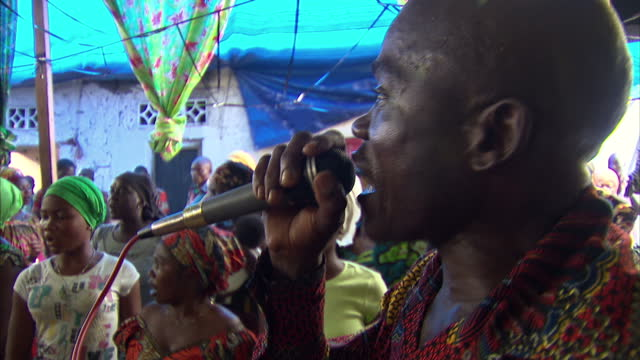 Exterior shots of a Congolese church service with worshippers singing and playing various musical instruments DR Congo General Views on February 14...
