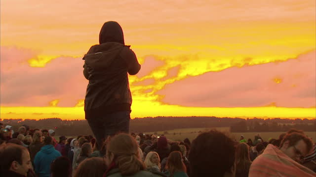 exterior shots of a crowd gathered at stonehenge watching the sun rise during summer solstice celebrations, some filming on cameras and mobile... - solstice stock videos & royalty-free footage