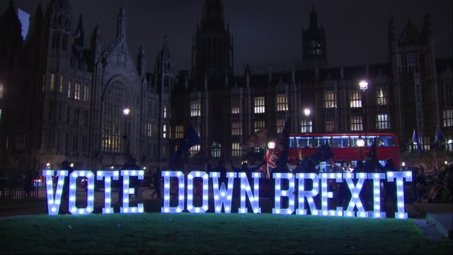 Exterior shots of a crowd of antiBrexit protesters with EU flags outside Parliament next to a large illuminated 'Vote Down Brexit' sign on 10...