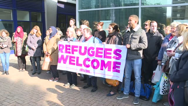 exterior shots of a crowd of pro-refugee demonstrators with banners reading 'refugees welcome' stood outside lunar house, home of the uk visas and... - ロンドン クロイドン点の映像素材/bロール