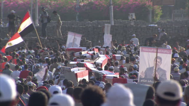 exterior shots of a crowd of protesters carrying coffins during protests after egyptian forces fired at pro morsi supporters on july 28 2013 in cairo... - mass murder stock videos & royalty-free footage