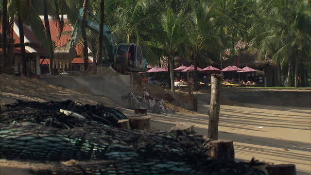 Exterior shots of a digger working on Khao Lak beach on construction site area with workers filling sand bags on the beach on August 29 2014 in Khao...