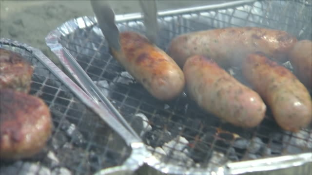 exterior shots of a disposable bbq grill with sausages and burgers being cooked, and a pack of paper plates and plastic cutlery on 28 may 2018 in... - slit och släng bildbanksvideor och videomaterial från bakom kulisserna