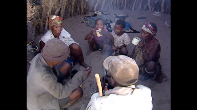 exterior shots of a family in a kalahari bush village sat in a makeshift enclosure around an open fire with a cooking pot on it, drinking tea and... - retrovirus stock videos & royalty-free footage
