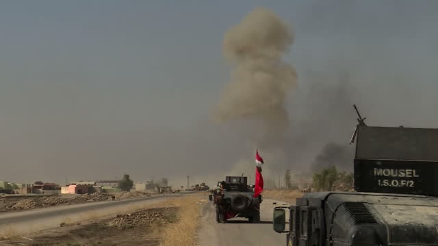 stockvideo's en b-roll-footage met exterior shots of a firefight between iraqi golden division soldiers and isis fighters with distant palls of smoke and iraqi humvees moving on... - isis