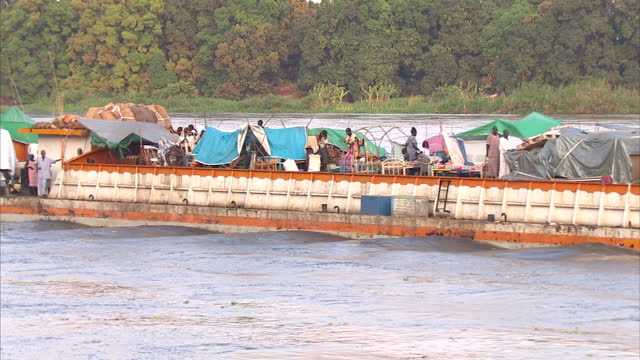 exterior shots of a fishing families sailing past on a large open barge with tent structures erected southern sudan's 2010 bid for independence on... - ジュバ市点の映像素材/bロール