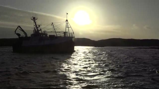 exterior shots of a fishing trawler docking at port on the isle of barra with a dramatic sunrise in the background and trawlermen preparing to unload... - 停泊する点の映像素材/bロール