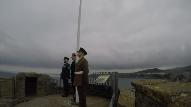 vídeos y material grabado en eventos de stock de exterior shots of a flag-raising ceremony attended by military personnel from all three services at scarborough castle as the red arrows perform a... - scarborough reino unido