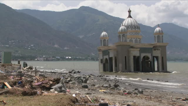 exterior shots of a flooded mosque building and wreckage, debris and dead livestock on a beach after the earthquake and tsunami on 5 october 2018 in... - java stock videos & royalty-free footage