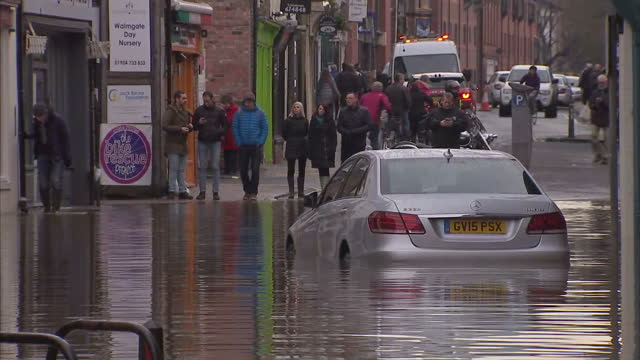 Exterior shots of a flooded street in York with local people looking on and the sound of an alarm going off in the background>> on December 28 2015...