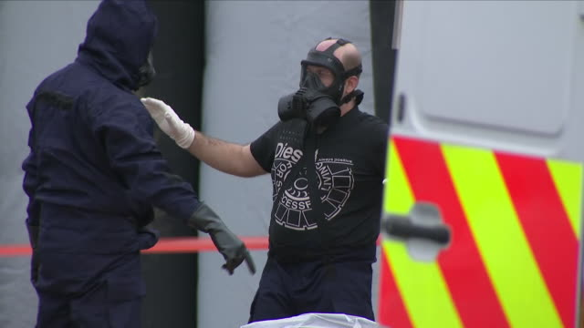 Exterior shots of a forensics officer wearing a gas mask and being inspected by another officer wearing protective clothing at the Ashley Wood...