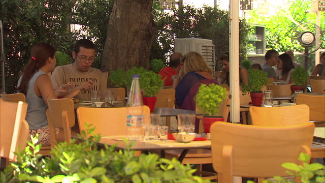 exterior shots of a fountain and seating area in a square, street scenes and people eating together at cafe restaurants on outdoor tables on july 10,... - greek food stock videos & royalty-free footage