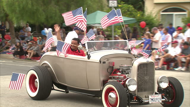 Exterior shots of a fourth of July carnival parade with crowds watching and waving flags a parade of bikers on Harley Davidson motorcycles and...