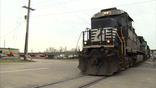 Exterior shots of a freight train driving along the tracks through Selma past a traffic crossing>> on March 07 2015 in Selma Alabama