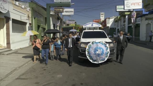 exterior shots of a funeral procession through the streets with mourners following a hearse on april 04 2018 in san salvador el salvador - 中央アメリカ点の映像素材/bロール