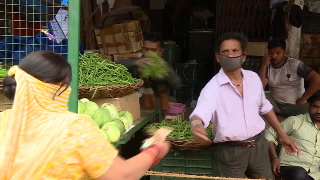 exterior shots of a greengrocer selling vegetables from a stand in a busy marketplace wearing a face mask on 25 march 2020 in delhi india - selling stock videos & royalty-free footage