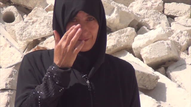 exterior shots of a grieving mother and widow walking amid rubble in aleppo and an interview with her, in arabic, on august 24, 2016 in aleppo, syria. - widow stock videos & royalty-free footage