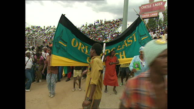 vídeos y material grabado en eventos de stock de exterior shots of a group of tribal dancers entertaining crowds and shots of anc banner declaring 1994 as 'the year of freedom' and 'democratic... - 1994
