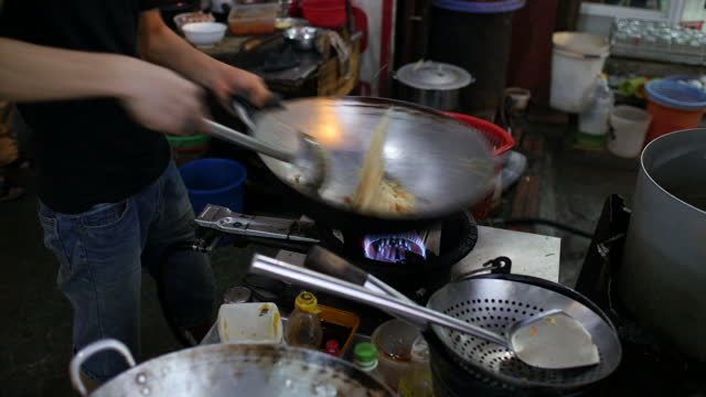 exterior shots of a hanoi street food stall with bun cha being prepared and served and customers sat at small tables eating on february 23, 2015 in... - pangolino video stock e b–roll