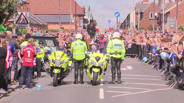 Exterior shots of a horse drawn hearse in Sunderland FC colours arriving at church surrounded by mourners on 14 July 2017 in Sunderland United Kingdom